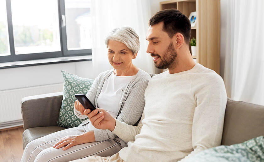 old mother and adult son with smartphone at home